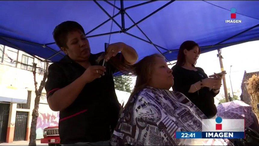 Mujer corta cabello en la calle por el sismo